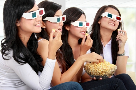 watching movie: group of woman friends watching movie wearing 3d glasses while having popcorn Stock Photo