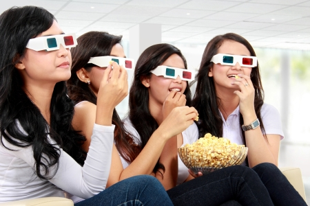 group of woman friends watching movie wearing 3d glasses while having popcorn photo