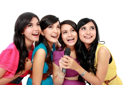 Four beautiful stylish woman singing karaoke together isolated over white background photo