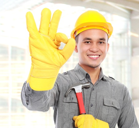 technical service: Portrait of young worker with tool belt giving you thumbs up Stock Photo