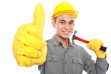 Portrait of young worker hold a hammer giving you thumbs up photo