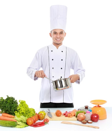 chef cooking: happy smiling male chef cooking in the kitchen