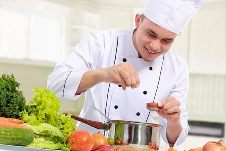 vegetable cook: felice sorridente chef maschio mettere qualche ingrediente in padella