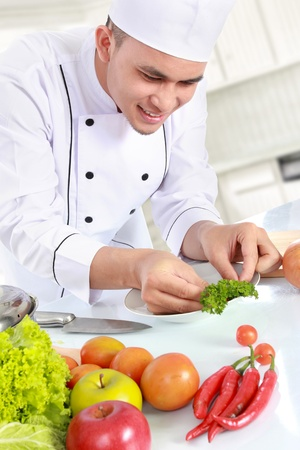 happy smiling male chef preparing by doing garnish on the plate photo