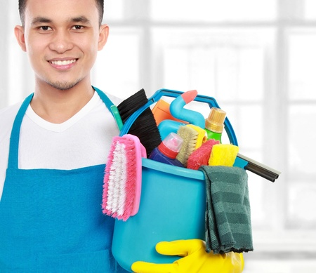 bright housekeeping: portrait of man with cleaning equipment ready to work