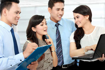 associates: group of happy business people doing presetation with laptop during meeting Stock Photo
