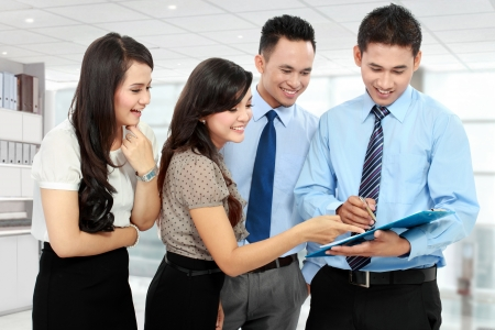 asian business team: group of happy business people doing presentation