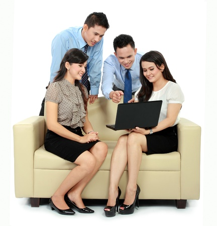 group of happy business people working on laptop during meeting photo