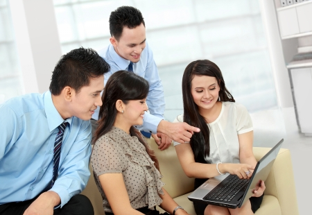 informal: group of happy business people working on laptop during informal meeting Stock Photo