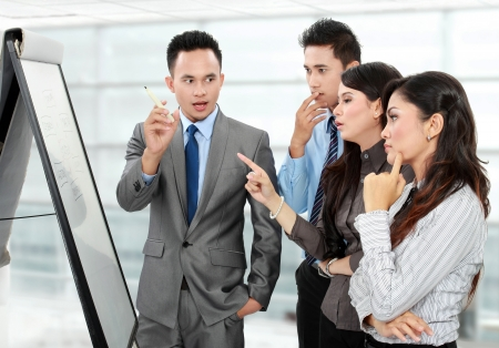 Group of business people discussing and looking at whiteboard in the office photo