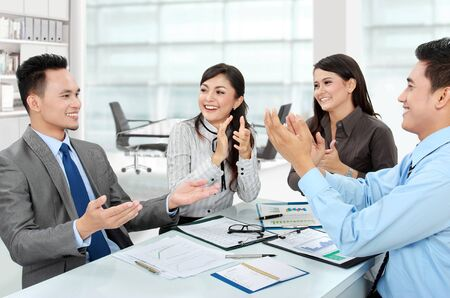 job promotion: Portrait of a woman and man office workers  clapping salute their team