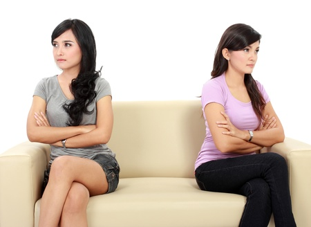 difficult lives: two woman hates each other. sitting on the couch