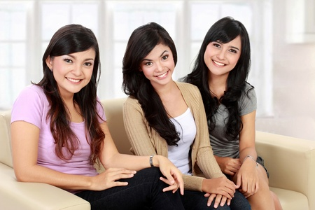 Group of beautiful asian women smiling while sitting on the couch photo