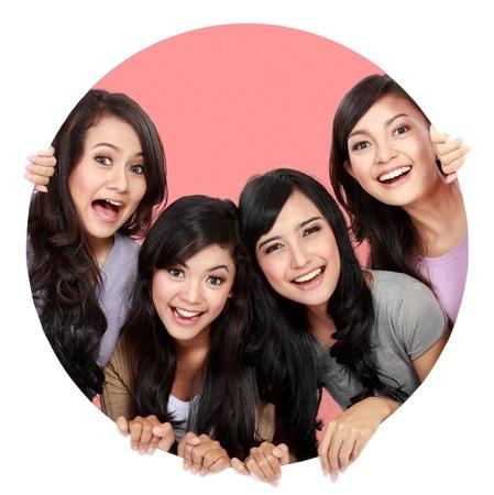 mejores amigas: Grupo de mujeres hermosas sonrientes asomando por el agujero círculo. bueno para su diseño Foto de archivo