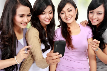 four beautiful young women friends at home using mobile phone together photo