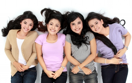 woman in white: four young attractive asian women relaxing smiling lying on the floor Stock Photo