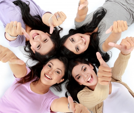 friends laughing: four young attractive asian women relaxing smiling lying on the floor showing thumbs up