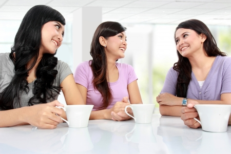 group of women friends chatting over coffee at home photo