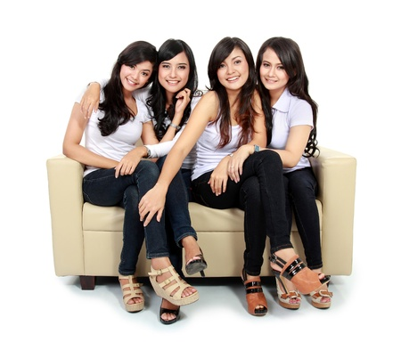 group of young adults: Group of beautiful asian women smiling together sitting on the couch isolated over white background Stock Photo