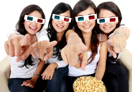 girl friends sitting on couch watching movie in 3d. pointing to the camera photo