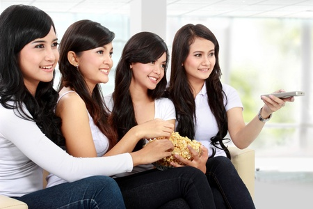 woman friends sitting on couch watching  tv together photo