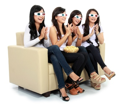 friends sitting on couch watching and applause at the movie in 3d photo