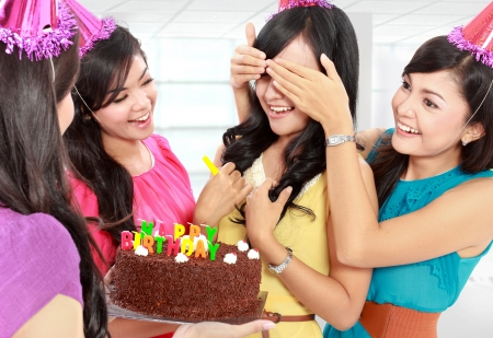 surprise party: young beautiful woman blindfold during surprise birthday party