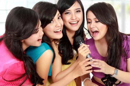 karaoke singer: Four beautiful stylish woman singing karaoke together