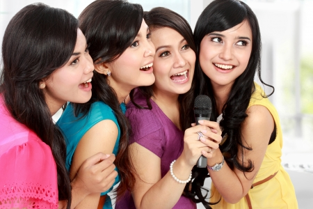 Four beautiful stylish woman singing karaoke together photo