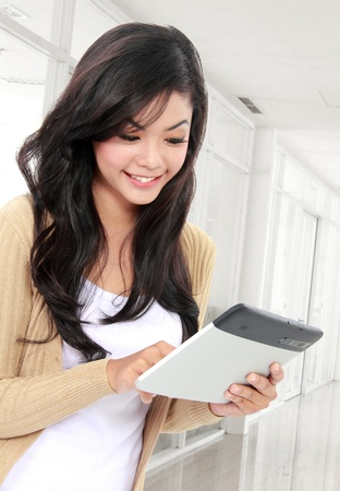 casual  smiling teenager touching tablet PC. photo