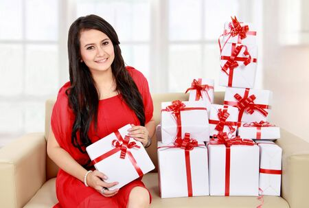 portrait of smiling young girl sit on sofa and some gift  beside her Stock Photo - 17889515