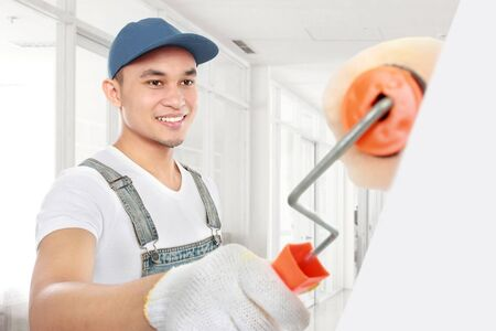 office uniform: Painter painting the office wall with roller paint Stock Photo