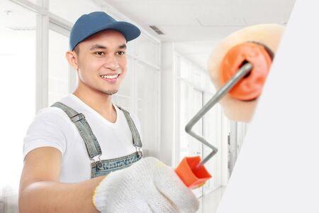 Office uniforms: Pintor pintando la pared de la oficina con el rodillo de pintura Foto de archivo