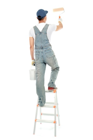 painter on the ladder painting the wall isolated on white background photo
