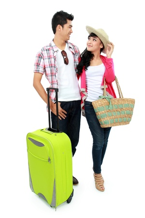 outfit: happy young boy and young girl bringing suitcase going on vacation