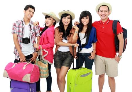 Grupa młodych ludzi, przynosząc torbę i walizkę się na wakacje