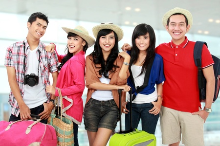 bringing: group of young people bringing bag and suitcase going on vacation