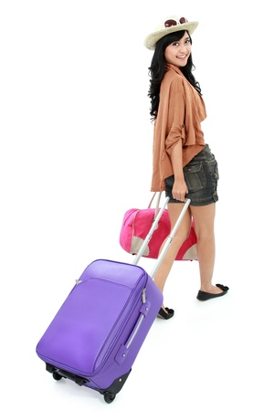 portrait of Happy girl going on vacation walking with suitcase and smile photo