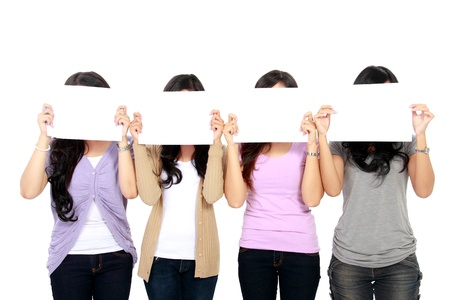 portrait of four teenage girls holding a white board and cover their faces photo