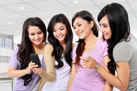 telephone together: group of girls looking at phone together