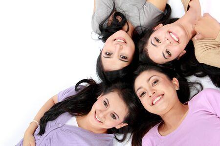 asian women: four teenage girls lying on the floor smiling