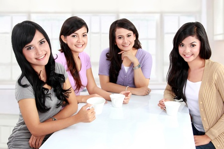 group of women friends having tea  together at home photo