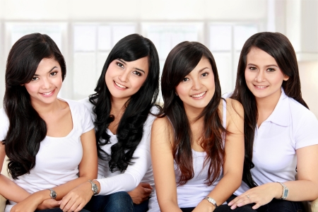 teen love: Group portrait of asian girls in the living room Stock Photo