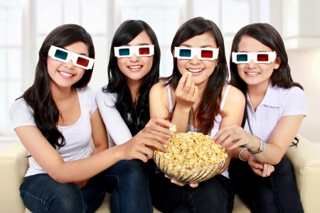 Group of girls watching movie wear 3D glasses while eating popcorn photo