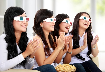 Group of girls clapping watching good 3D movie in home theater photo