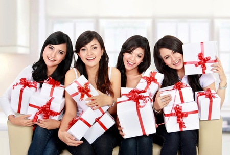 house party: group of happy Beautiful young woman with many gift boxes sitting on the sofa