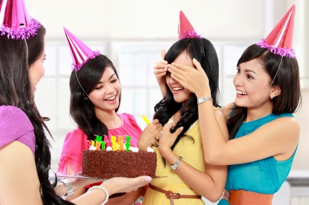 young beautiful woman blindfold during surprise birthday party photo