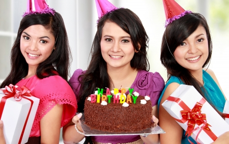 three gift boxes: three young beautiful girls celebrate birthday with cake and gift boxes at home