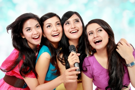Four beautiful young woman singing karaoke together photo