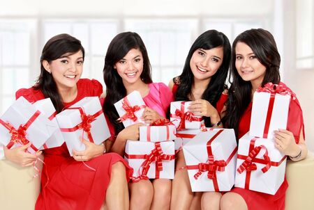 clothing model: group of Beautiful young woman dress in red with many gift boxes sitting on the sofa
